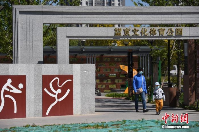 市民带着孩子经过北京市朝阳区望京文化体育公园。<a target='_blank' href='http://www.chinanews.com/'><p  align=