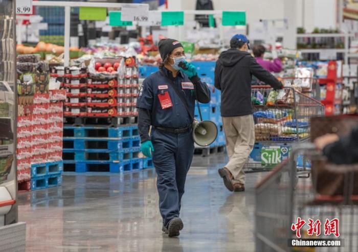 """当地时间4月22日,一位做事人员用扩音设备重复挑醒顾客佩戴口罩以及保持""""外交距离""""。中新社记者 刘关关 摄"""