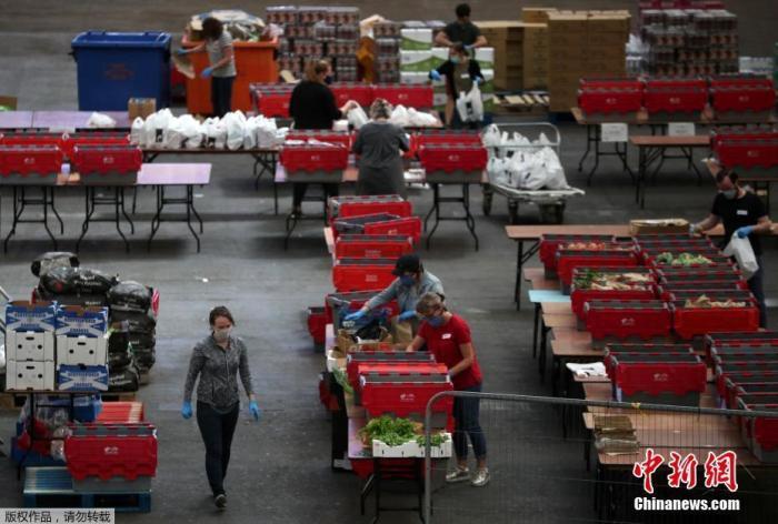"""当地时间4月21日,志愿者在位于英国伦敦北部亚历山德拉宫内的一处食品发放处忙碌。在新冠疫情期间,平时主要作为举办展览和赛事场地的英国伦敦亚历山德拉宫""""变身""""食品发放处,供一些民间慈善机构和社区组织为需要帮助的群体提供援助。"""