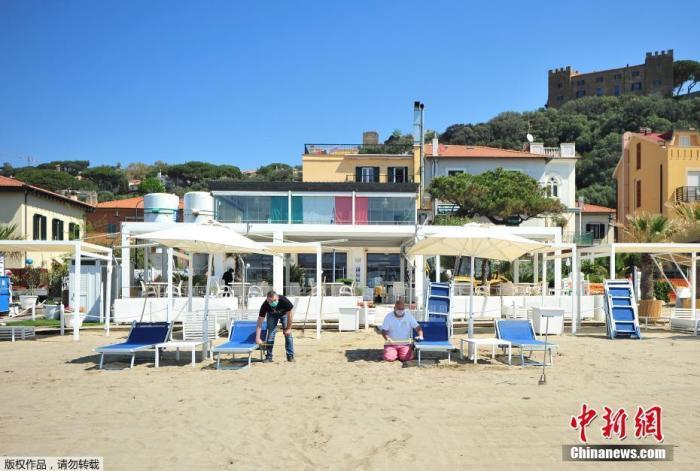 当地时间4月24日,意大利一海滩俱乐部的工人戴着口罩和手套为度假区的重新开业做准备。