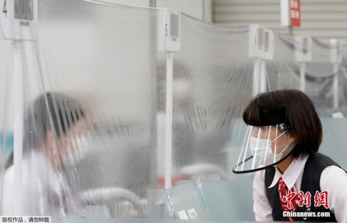 日本疫情形势依旧严峻。图为东京一家银行内,戴口罩的工作人员隔着塑料布与银行柜员交流。