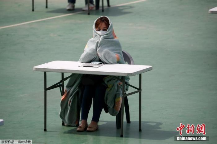 当地时间4月25日,韩国为了避免新型冠状病毒传播,在露天操场为求职者举行入职考试。图为参加考试的人裹着毛毯取暖。