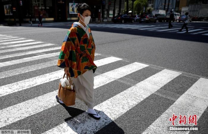 """""""居家周""""时间为4月25日至5月6日,共12天。东京都呼吁民众在这段时间里进一步减少外出,主动留在家中。图为穿和服的女士走过银座购物区的路口。"""