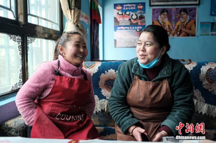 4月24日,樟木新区住民顿卓玛(左)和姑妈在自家餐馆谈天。 /p中新社记者 何蓬磊 摄