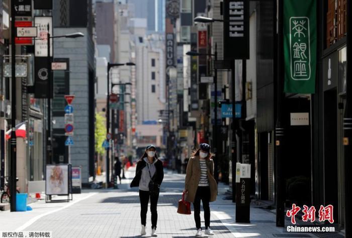 日本进入紧急状态后,外出行人减少。图为当地时间4月25日,戴口罩的女士走过东京空无一人的购物区。