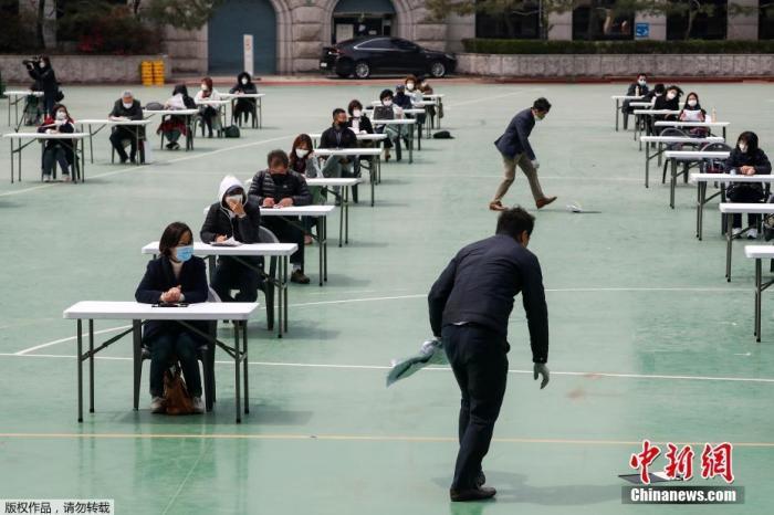 当地时间4月25日,韩国为了避免新型冠状病毒传播,在露天操场为求职者举行入职考试。图为监考人员在地上捡起被风吹掉的文件。