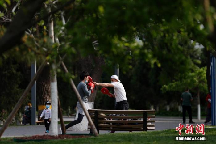 4月26日,拳击健身教练伊力夏提(右)带领学员在北京龙潭公园内练拳。新冠肺炎疫情发生后,伊力夏提所在的健身俱乐部暂时停业,他带领学员在公园坚持锻炼。<a target='_blank' href='http://www.chinanews.com/'>中新社</a>记者 富田 摄