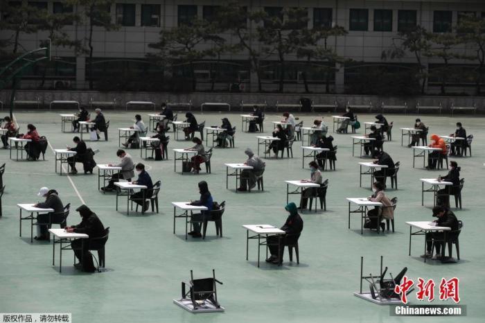 当地时间4月25日,为了防止新冠病毒传播,韩国保险从业人员在户外进行了一场资格考试。考场设在一个学校的露天操场上,所有考生进入考场时,必须先测量体温。在考试期间,考生和监考人员必须佩带口罩,座位之间保持至少1.5米的距离。