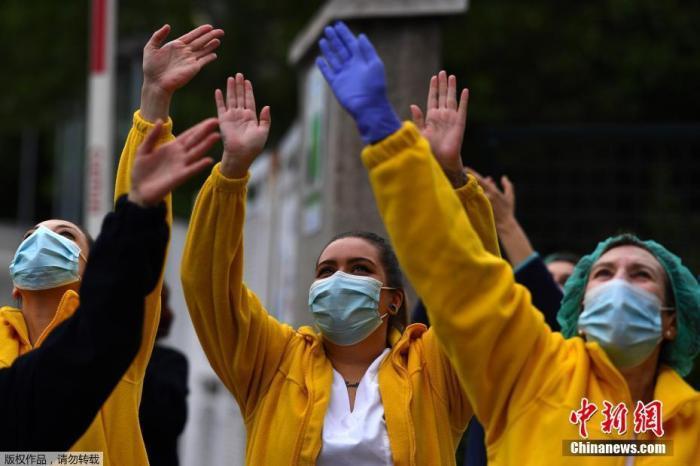 當地時間4月27日,在西班牙馬德里的一家醫院外,醫護人員在為全國禁閉期間居家隔離的民眾們鼓掌歡呼,為他們加油打氣。