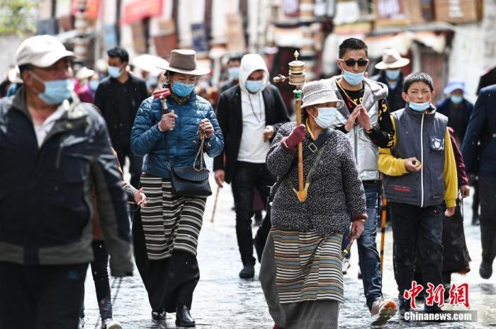 4月28日,信众手摇转经筒,顺着八廓街转经祈福。 何蓬磊 摄