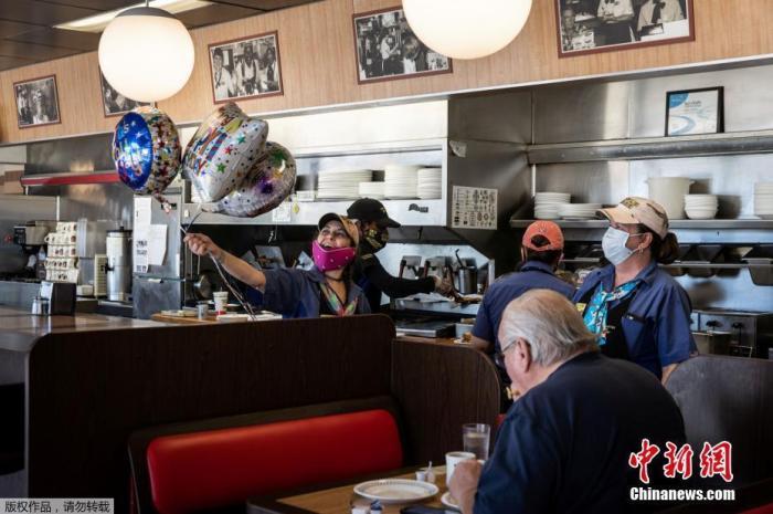 """当地时间4月27日,位于美国佐治亚州麦迪逊市的一家华夫饼店员工庆祝""""复工""""。"""