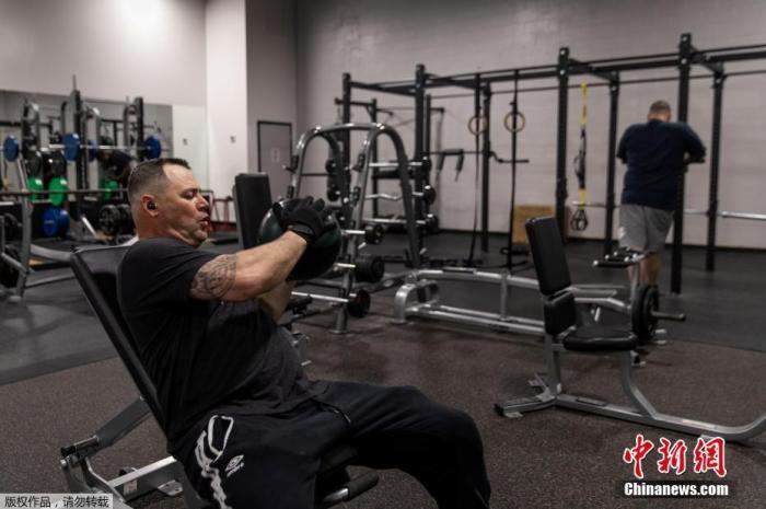 """资料图:内地时间4月27日,美国佐治亚州奥古斯塔,一家连锁健身房从头开业,部门公众回归""""撸铁""""糊口。"""