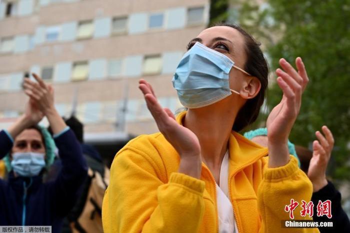 当地时间4月27日,在西班牙马德里Ψ 的一家医院外,医护人员在为全国禁闭期间№居家隔离的�|民众们鼓掌欢呼,为他们加油打�z气。