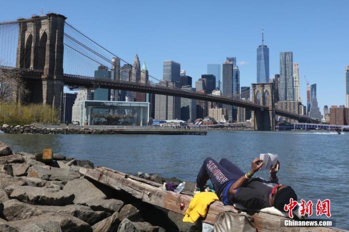 当地时间4月28日,一位市民在纽约布鲁克林大桥下戴着口罩看书。据美国约翰斯·霍普金斯大学实时统计数据,截至北京时间4月29日1时30分,美国新冠肺炎累计确诊病例已超过100万例。中新社记者 廖攀 摄