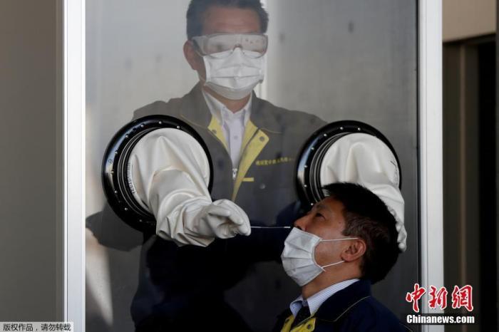 资料图:日本横须贺市,医务人员在一个箱状的临时检疫设施中模拟对人们进行核酸检测。