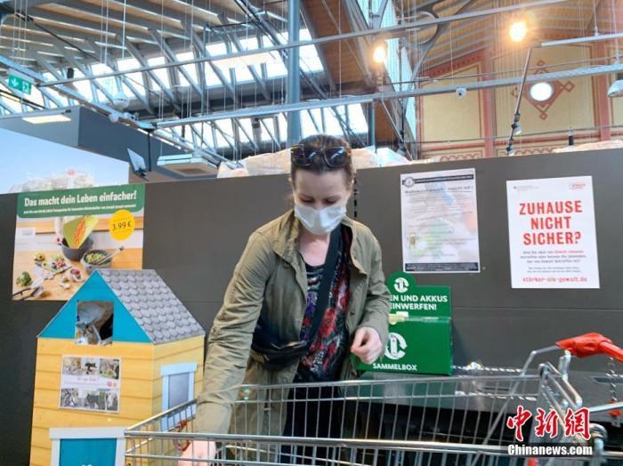 """4月29日,德国柏林市政府开始将该市""""口罩强制令""""的范围从此前仅限于公共交通工具扩大至包含超市和各类零售商店。柏林是德国16个州中最后一个实施""""购物和出行均必须佩戴""""的州。图为当天下午,柏林市中心的REWE超市一名戴口罩的顾客。<a target='_blank' href='http://www.chinanews.com/'>中新社</a>记者 彭大伟 摄"""