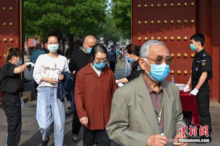 5月1日,游客佩戴口罩进入北京景山公园游览。中新社记者 崔楠 摄