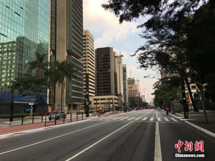 """当地时间5月1日,在巴西圣保罗,宽敞的保利斯塔大街上行人稀少。在""""五一""""国际劳动节这一天,巴西最大城市圣保罗仍处于因疫情实施的""""社会隔离""""期,街上商店紧闭,行人稀少。<a target='_blank' href='http://www.mubaka.com/'>中新社</a>记者 莫成雄 摄"""
