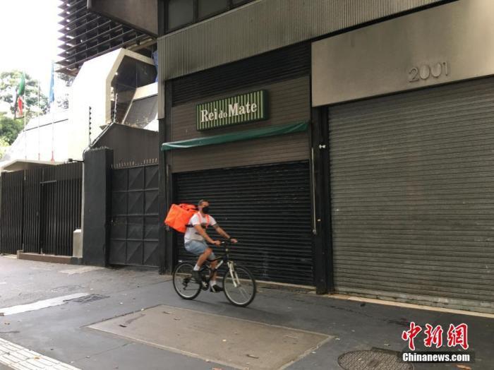 """当地时间5月1日,在巴西圣保罗,一名快递员骑车从几间关门的店铺前经过。在""""五一""""国际劳动节这一天,巴西最大城市圣保罗仍处于因疫情实施的""""社会隔离""""期,街上商店紧闭,行人稀少。/p中新社记者 莫成雄 摄"""