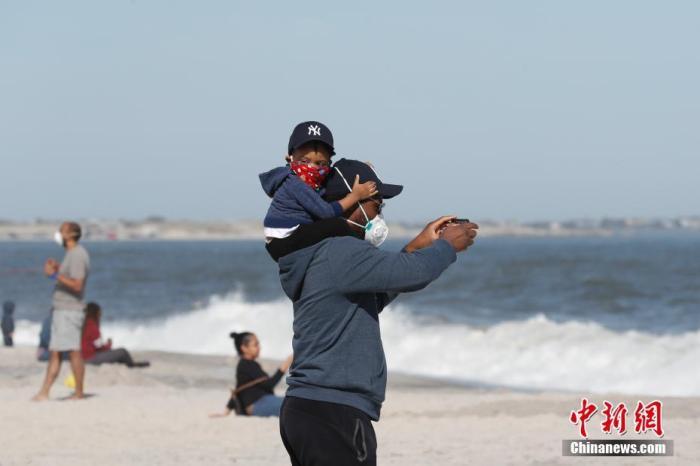 当地时间5月2日,美国纽约州长岛琼斯海滩上的父子。据美国约翰斯・霍普金斯大学发布统计数据,截至2日晚,美国累计新冠肺炎确诊病例已经超过113万例,其中纽约州确诊病例超过31万例。中新社记者 廖攀 摄