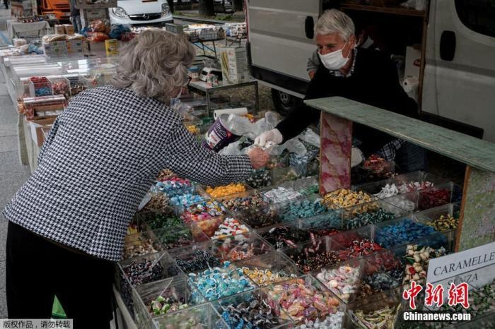 """当地时间5月5日,曾经被列为意大利疫情""""红区""""的北部小镇圣菲奥拉诺逐步解封,一位民众正在糖果摊购物,这是该市场从2月21日关闭后首次开放。"""