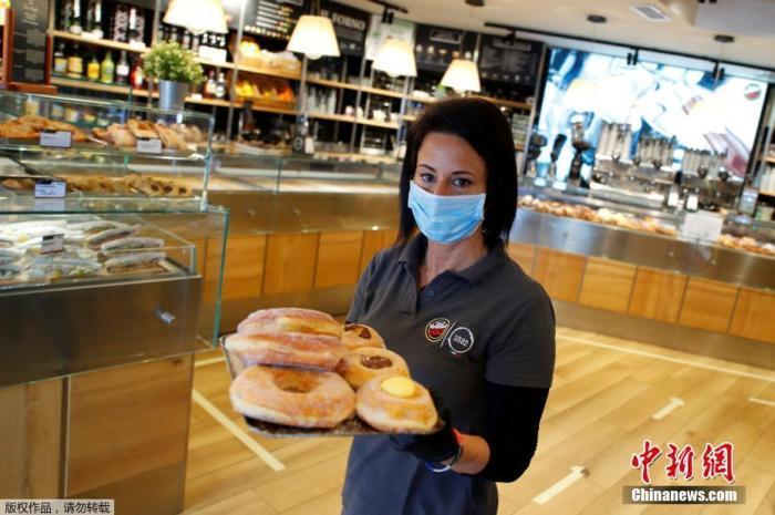 意大利首都罗马的一家咖啡馆里,一名戴着防护口罩和手套的咖啡师端着满满一盘甜品,目前这家咖啡馆只接受外卖。