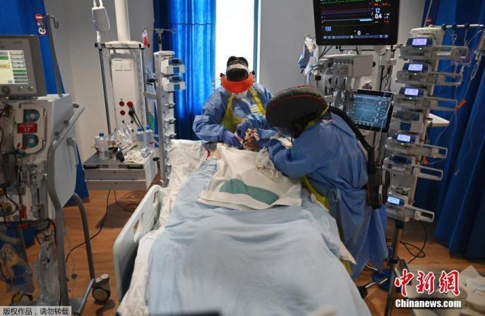 图为英国新冠病人重症监护室内,医护人员在照顾患者。