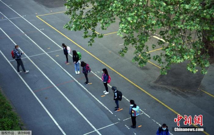 当地时间5月7日,德国西部,多特蒙德的Petri小学学生开学复课,老师在操场为学生讲社交安全距离规则。