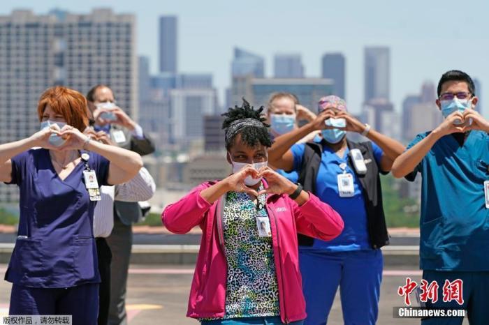 """当地时间5月6日,美国达拉斯,美国海军""""蓝天使""""飞行表演队飞过之后,部分医疗人员在赫尔曼纪念医院的直升机停机坪上合影。"""