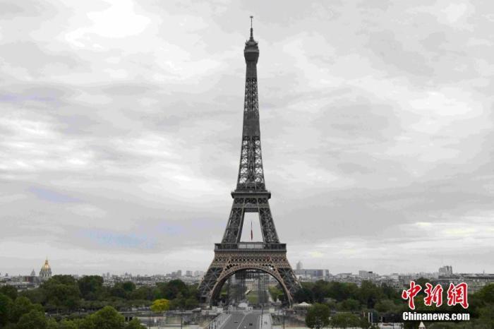 """当地时间5月8日,法国仍处于""""封城""""等管制措施中,为防控新冠肺炎疫情,官方纪念二战胜利75周年活动低调进行。埃菲尔铁塔当天悬挂起巨幅法国国旗。中新社记者 李洋 摄"""