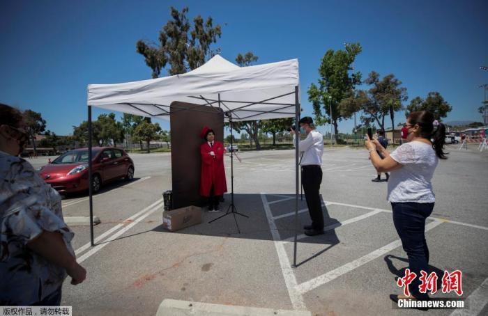 当地时间5月8日,美国加州帕萨迪纳市,受疫情影响,当地高中毕业生无法在校完成毕业照,一个路边工作室为这些毕业生解决了毕业照拍摄的问题。