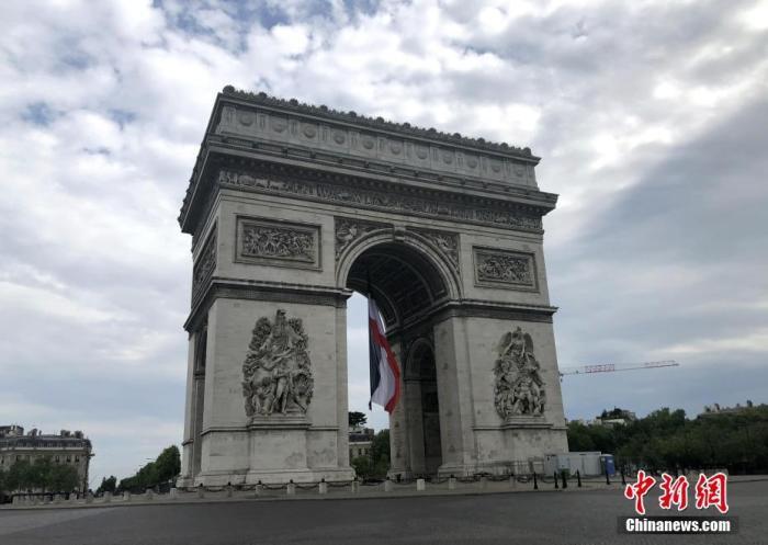 """当地时间5月8日,法国仍处于""""封城""""等管制措施中,为防控新冠肺炎疫情,官方纪念二战胜利75周年活动低调进行。在凯旋门拱门上方当天悬挂起巨幅法国国旗。中新社记者 李洋 摄"""