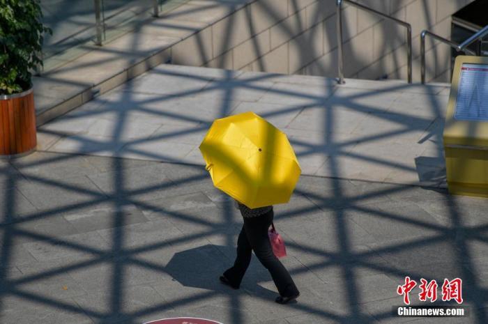 资料图:民众撑伞出行抵烈日。 骆云飞 摄