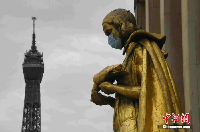 """当地时间5月8日""""欧洲胜利日""""拍摄的雕塑,背景为埃菲尔铁塔。法国将于5月11日起逐步""""解封"""",为了提醒民众""""解封""""后注意防护,巴黎著名景点夏洛宫外的金色雕塑被戴上了口罩。<a target='_blank'  data-cke-saved-href='http://www.chinanews.com/' href='http://www.chinanews.com/'>中新社</a>记者 李洋 摄"""