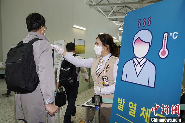 """资料图:5月10日,210多名韩国企业员工启程前往中国天津复工。他们是首批申请通过""""快捷通道""""入境中国的韩方人员。图为仁川机场,韩企员工登机前接受体温检查。 中新社记者 曾鼐 摄"""