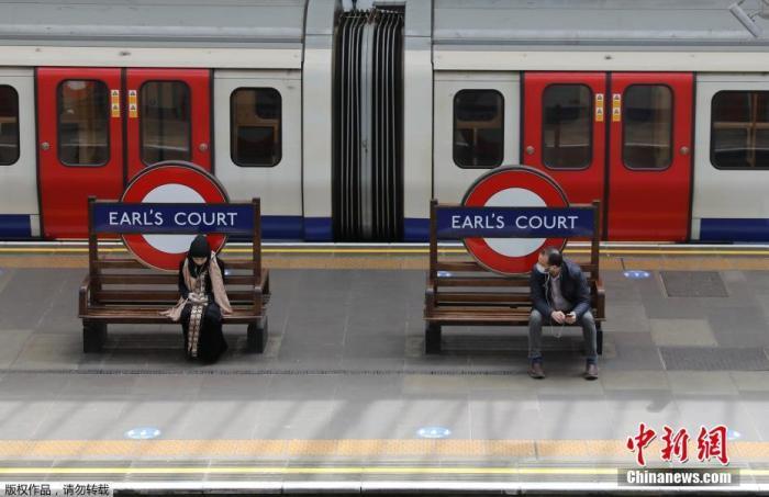 當地時間5月11日,英國倫敦,出行的市民坐在伯爵法院站的長凳上。