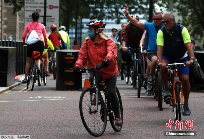 """资料图:英国首相宣布有条件""""解封""""当地民众骑自行车穿过伦敦的威斯敏斯特地区。"""