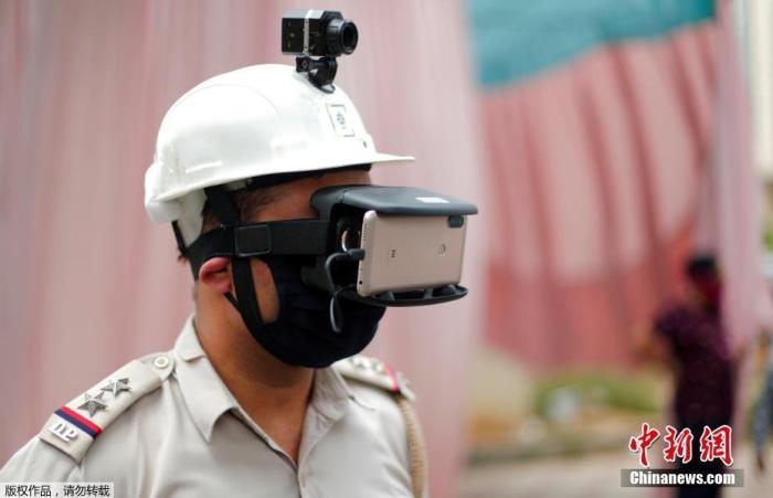 当地时间5月11日,印度新德里街头,为防止新冠肺炎疫情的扩散,警察带着一款特制头盔上岗,头盔顶端设有监控器,面部用除佩戴口罩外,还有一款链接手机的智能眼罩,只需看一眼就知道行人体温是否正常。