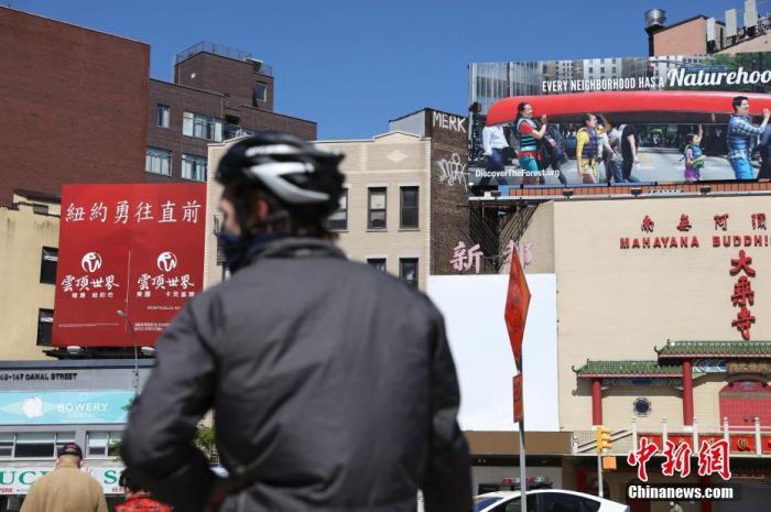 """当地时间5月12日,纽约曼哈顿唐人街,一个广告牌上写着""""纽约勇往直前""""。记者 廖攀 摄"""