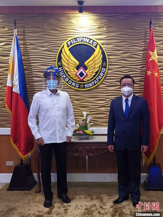 5月12日深夜,载着援助菲军抗疫物资的中国军用运输机,飞抵马尼拉诺伊·阿基诺国际机场。在菲维拉莫空军基地,中国驻菲律宾大使黄溪连(右)和菲律宾国防部长洛伦扎纳(左),共同出席了中国国防部援助菲军抗疫物资交接仪式。 中新社发 中国驻菲律宾使馆供图