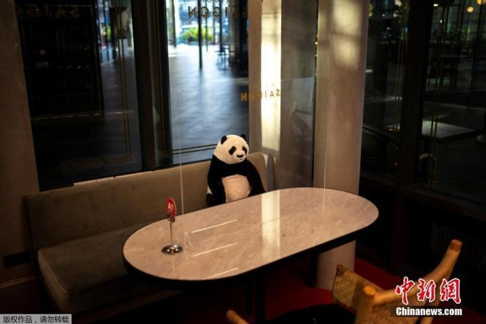 当地时间5月13日,泰国曼谷放宽限制措施后,为防止新型冠状病毒蔓延,一家餐厅推出大熊猫玩偶陪顾客吃饭。图为坐在餐椅上的大熊猫玩偶。