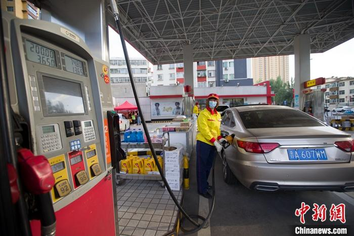 资料图:加油站工作人员给车辆加油。记者张云摄