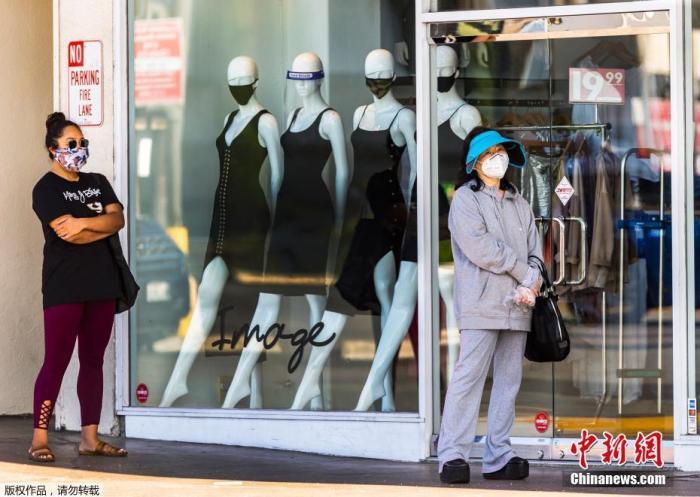 当地时间5月13日,洛杉矶市长贾西提宣布,为了保障安全,人们只要出门就必须戴口罩。图为洛杉矶市民戴着口罩在一商店前排队。