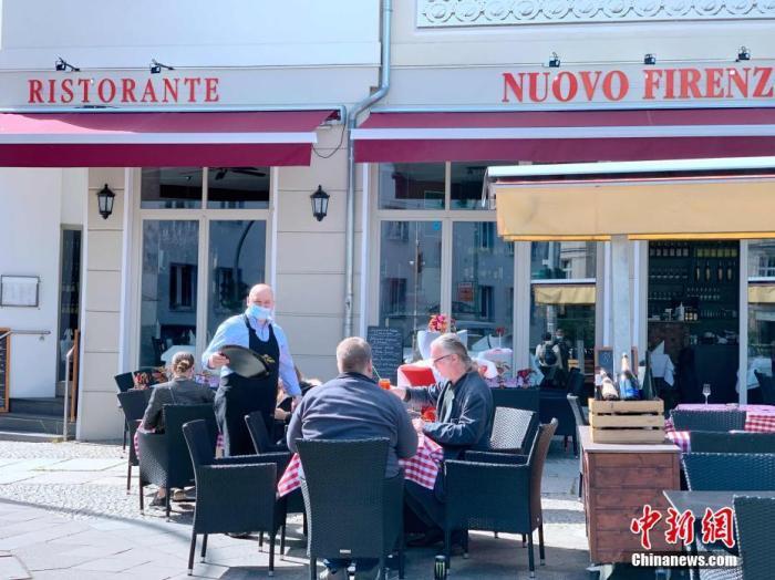 图为5月15日中午,柏林米特区一家意大利餐厅恢复营业后,服务员佩戴了口罩,顾客则在户外用餐。 <a target='_blank' href='http://cdnzw.com/'>中新社</a>记者 彭大伟 摄