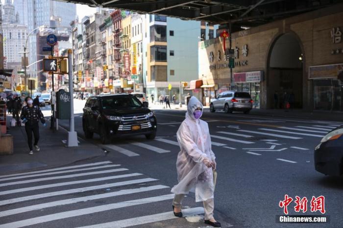 """5月12日,纽约市曼哈顿唐人街,一名""""全副武装""""的女子正在过马路。 /p中新社记者 马德林 摄"""