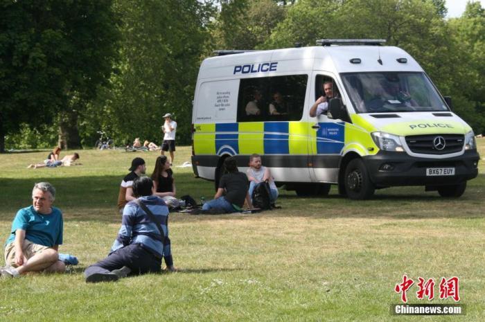 """当地时间5月17日,英国迎来了""""有条件解封""""后的首个周日,在伦敦,不少市民在户外享受休闲时光,警察驾驶警车在公园中四处巡查,劝告民众""""保持两米社交距离""""。 <a target='_blank' href='http://www.chinanews.com/'>中新社</a>记者 张平 摄"""