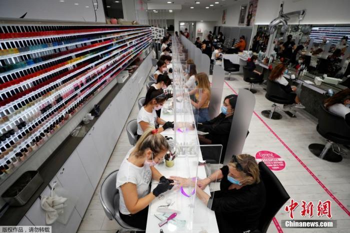 """近期,意大利社会逐步""""重启""""。图为当地时间5月18日,意大利罗马一家美发店内,大量顾客前来做指甲护理。"""