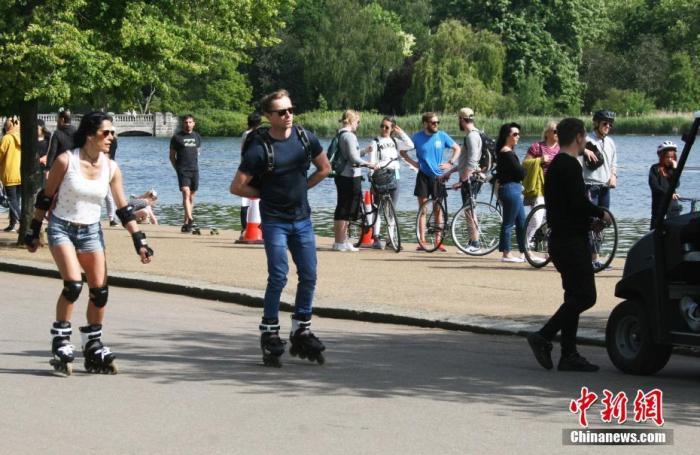 """当地时间5月17日,英国迎来了""""有条件解封""""后的首个周日,在伦敦,轮滑喜欢好者在街头滑走,享福息闲时光。 中新社记者 张平 摄"""