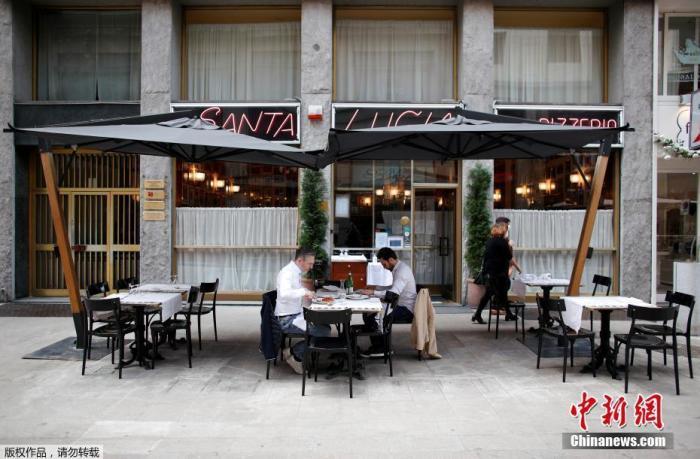 资料图:当地时间5月18日,意大利米兰,顾客坐在餐厅的露台上就餐。