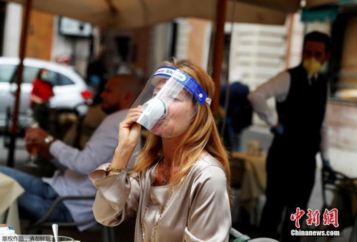 """意大利当局将依照打算5月18日开始松绑禁令,重启社会出产策划勾当,并开放相关旅游、游乐等公家设施。零售、餐饮及美容美发场合被要求于5月18日才气从头开放,这也被视为迈向""""苏醒之路""""的重要一步。图为戴面罩的密斯在罗马陌头喝咖啡。"""